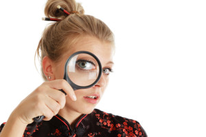 Young woman looking through a magnifying glass isolated over white